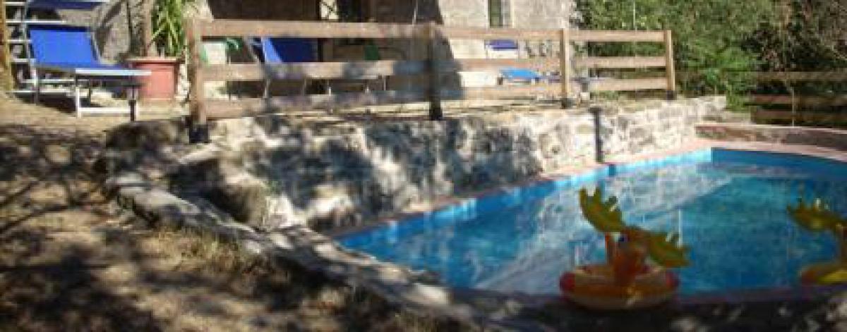 Beim Ferienhaus ist ein kleiner Pool mit Liegen